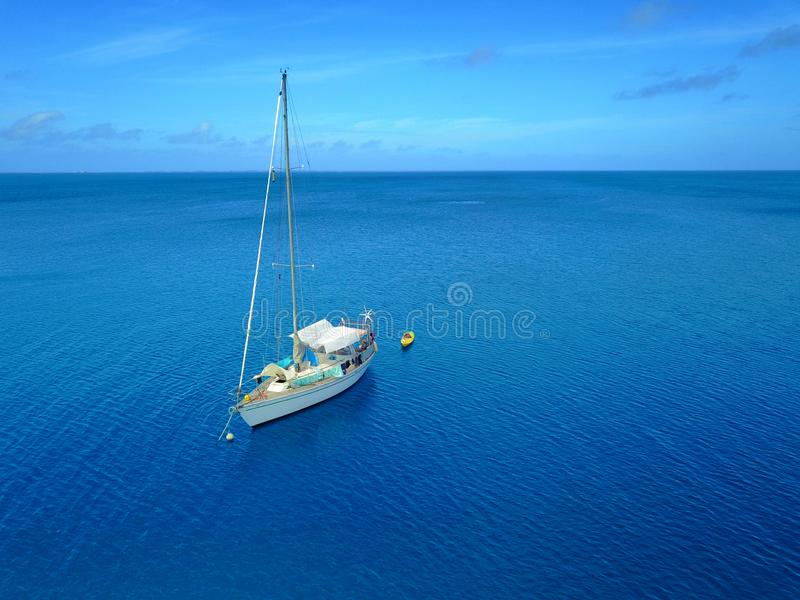 Tiro aéreo de um veleiro amarrado em uma lagoa tropical calma imagens de stock