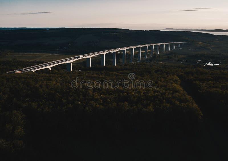 Tiro aéreo de uma ponte de arco de aço construída em uma floresta imagens de stock royalty free