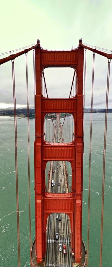 Tiro aéreo de uma ponte de suspensão vermelha com algum tráfego sobre sobre um grande rio bonito imagens de stock royalty free
