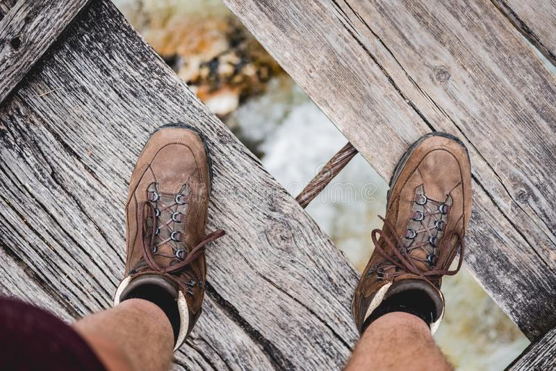 Tiro aéreo de uma posição masculina dos pés em uma ponte de madeira que veste caminhando sapatas imagens de stock royalty free