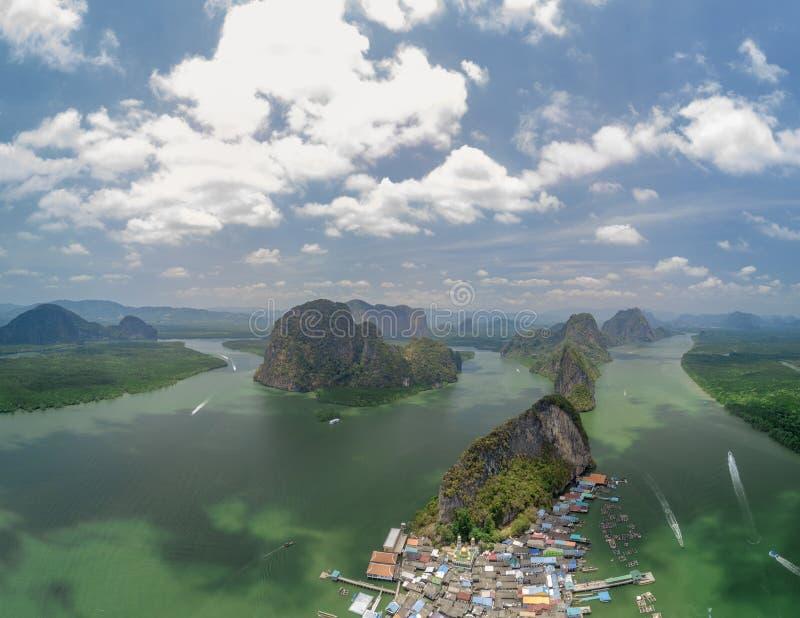 Tiro aéreo de uma vila e de umas ilhas elevando-se do panyi do Koh, Tailândia imagens de stock royalty free