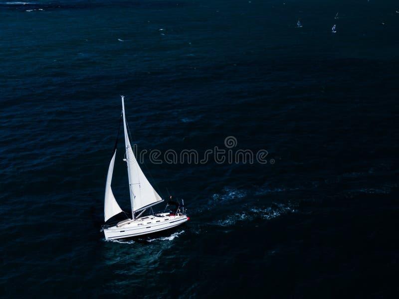 Tiro aéreo de una pequeña navegación blanca del barco en el océano fotos de archivo libres de regalías