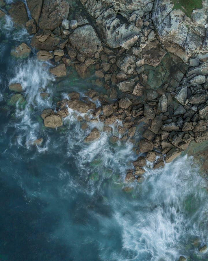 Tiro aéreo de una playa rocosa con las aguas que salpican que lavan las piedras imagenes de archivo