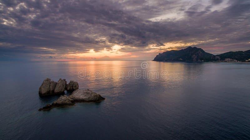 Tiro aéreo del abejón de una puesta del sol hermosa en la costa de Corfú central Grecia foto de archivo
