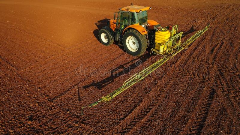 Tiro aéreo del granjero con un tractor en el campo agrícola foto de archivo libre de regalías