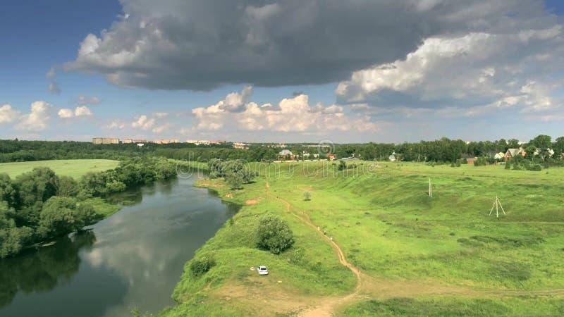 Tiro aéreo del río de Moskva cerca de Zvenigorod y de un pueblo en un día de verano parcialmente nublado, Rusia fotografía de archivo libre de regalías