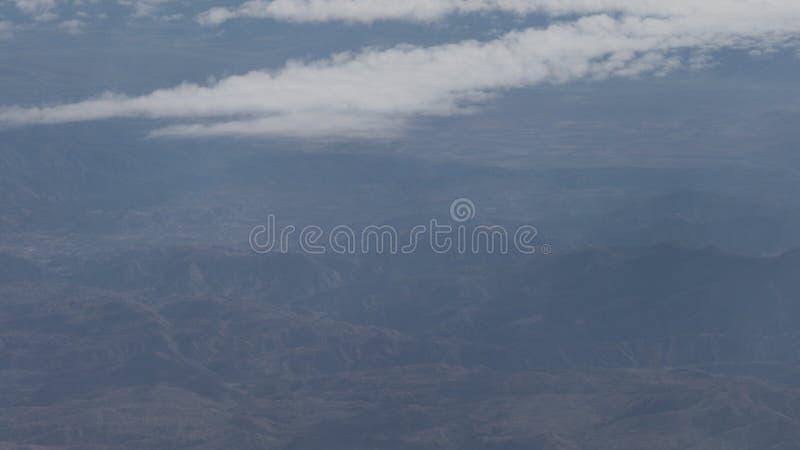 Tiro aéreo del vuelo plano sobre las montañas en d3ia foto de archivo