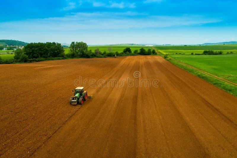 Tiro aéreo do fazendeiro com um trator no campo agrícola foto de stock
