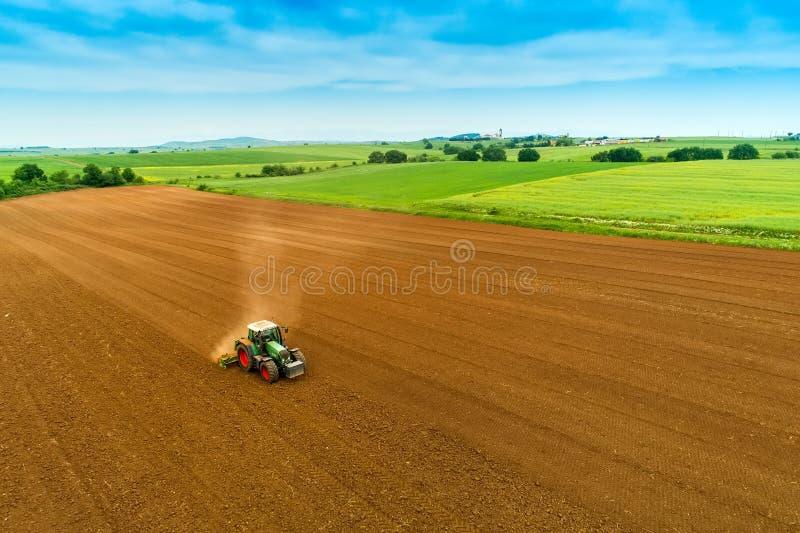Tiro aéreo do fazendeiro com um trator no campo agrícola imagem de stock