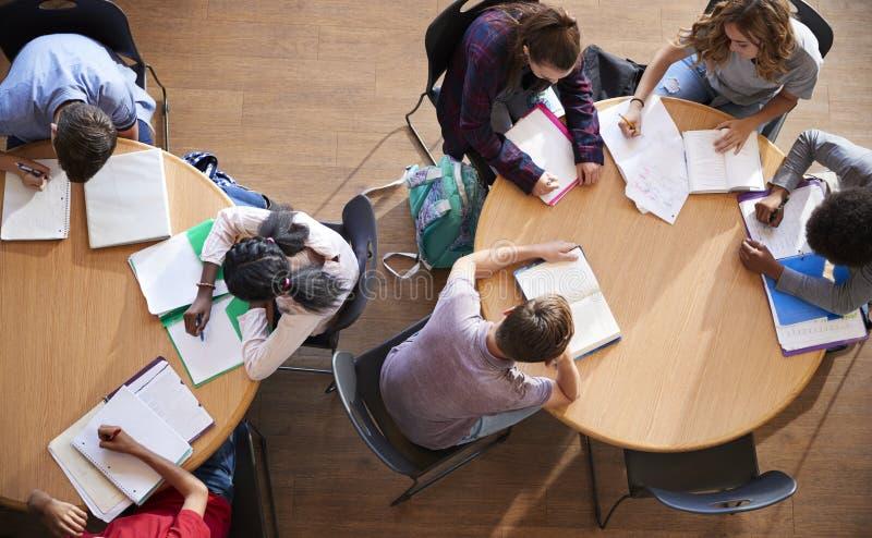 Tiro aéreo dos alunos da High School no estudo do grupo em torno das tabelas foto de stock