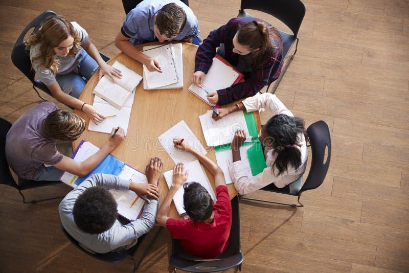 Tiro aéreo dos alunos da High School no estudo do grupo em torno das tabelas imagem de stock