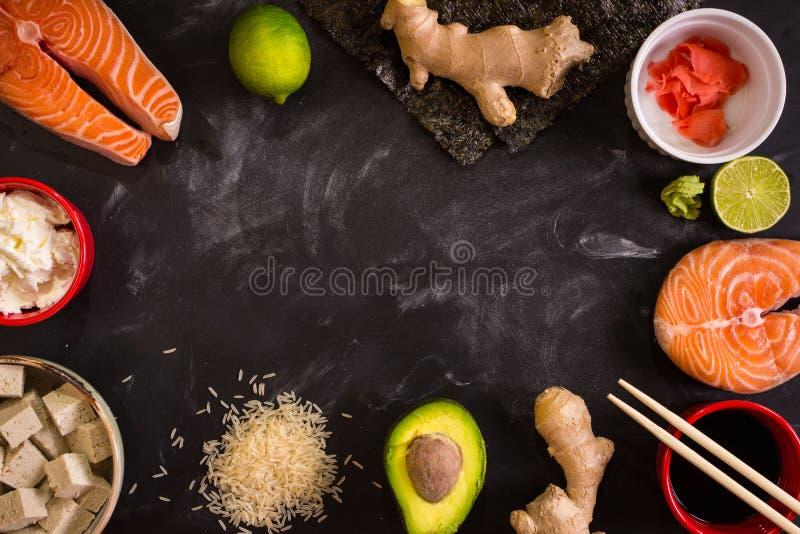 Tiro aéreo dos ingredientes para o sushi no fundo escuro imagem de stock