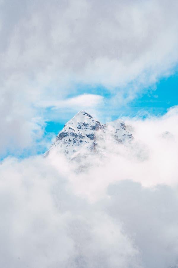 Tiro aéreo hermoso de un pico de montaña rodeado por las nubes impresionantes que sorprenden y el cielo azul fotografía de archivo libre de regalías