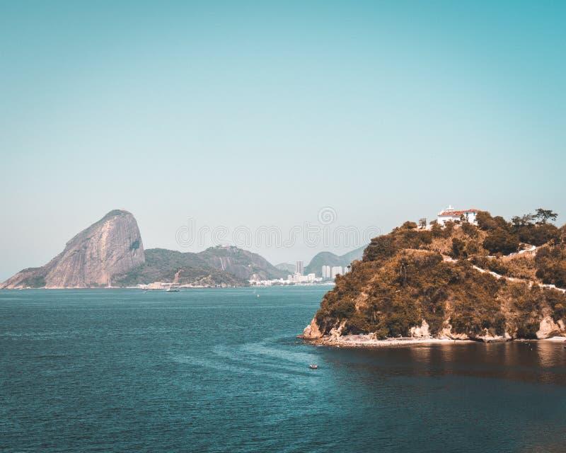 Tiro aéreo hermoso del mar con una mansión en una colina verde y de altas rocas en el fondo imagenes de archivo