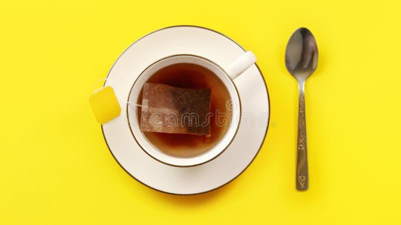 Tiro aéreo - o copo da porcelana com água quente, saquinho de chá apenas pôs dentro, manchando a colher líquida, de prata ao lado fotografia de stock