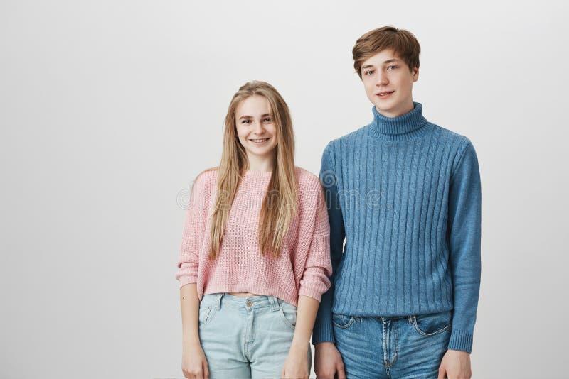 Tiro acogedor de los amigos caucásicos que llevan los suéteres hechos punto que presentan dentro Individuo del inconformista con  fotografía de archivo