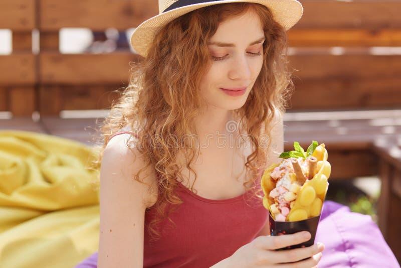 Tiro al aire libre de la chica joven linda romántica que mira su postre, estando en los ánimos, hambre de sensación, sosteniendo  fotos de archivo libres de regalías