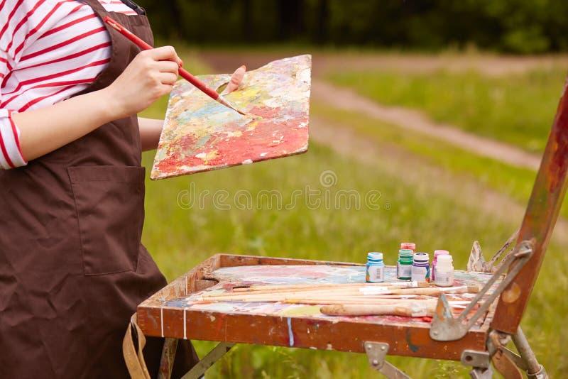Tiro al aire libre de la mujer desconocida alrededor de la naturaleza, del delantal marrón que lleva, sosteniendo el cepillo y la fotos de archivo libres de regalías