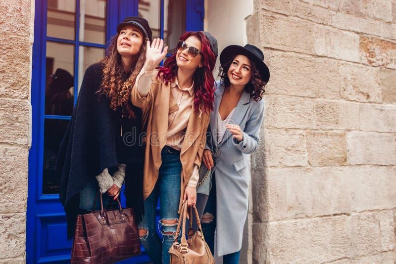 Tiro al aire libre de tres mujeres jovenes elegantes que miran en la distancia en la calle de la ciudad Amigos que ríen y que se  foto de archivo