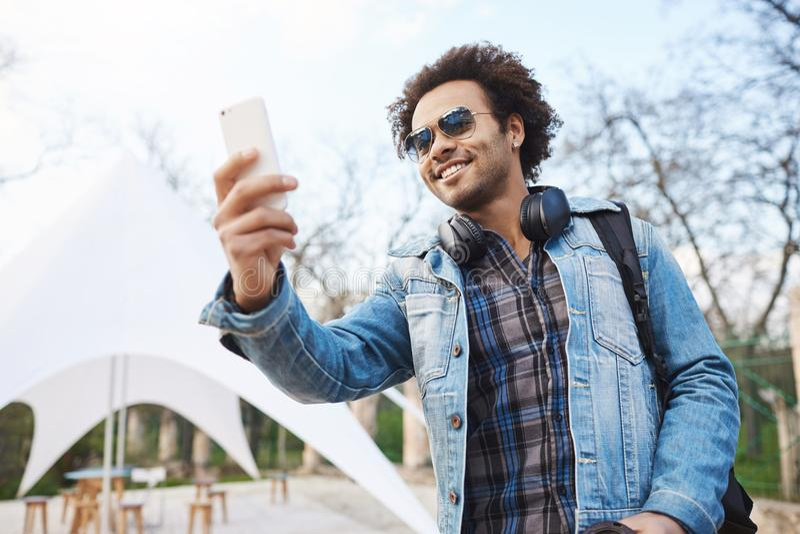 Tiro al aire libre del afroamericano joven atractivo con el peinado y los auriculares afro sobre cuello, ropa de moda que lleva fotografía de archivo