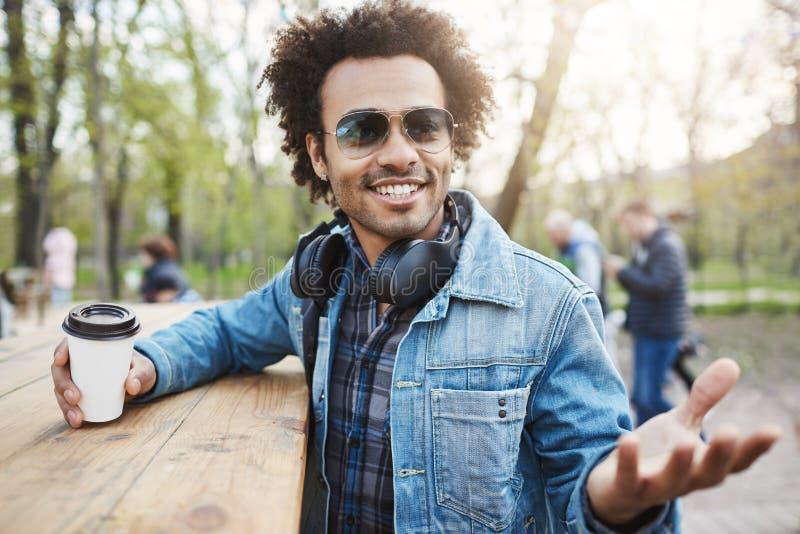 Tiro al aire libre del hombre de piel morena de moda con el peinado afro, los vidrios de moda que llevan y los auriculares sobre  fotografía de archivo libre de regalías