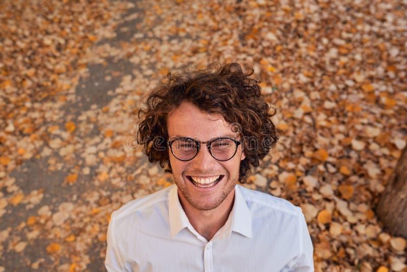 Tiro al aire libre del otoño del hombre de negocios joven hermoso sonriente con los vidrios al aire libre Estudiante masculino qu fotos de archivo