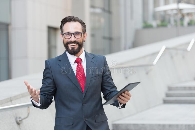 Tiro alegre do gerente de sorriso que está fora com uma tabuleta à disposição fotografia de stock royalty free