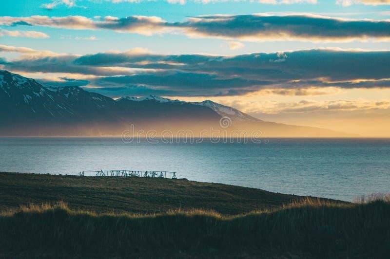 Tiro ancho de colinas verdes y de campos hermosos con el mar asombroso y nubes en el fondo imágenes de archivo libres de regalías