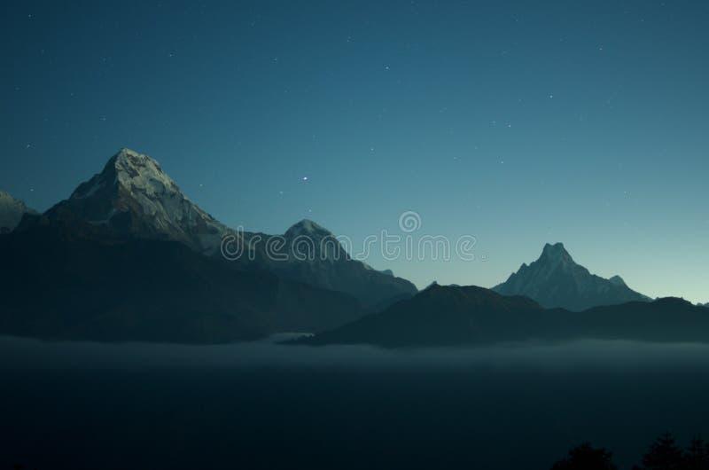 Tiro ancho de montañas rocosas hermosas con sorprender el cielo azul claro con las estrellas en el fondo fotografía de archivo
