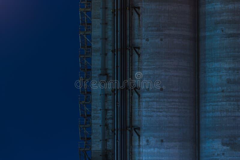 Tiro ancho de un edificio alto de la fábrica con la escalera del metal de la salida de socorro en el lado en fondo azul imagen de archivo