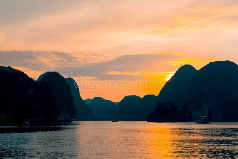 Tiro ancho hermoso de un lago con las altas colinas y puesta del sol detrás con las nubes que sorprenden fotos de archivo libres de regalías
