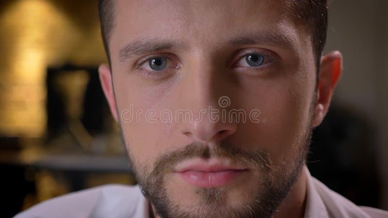 Tiro anteriore del primo piano del fronte maschio barbuto caucasico adulto con gli occhi che esaminano macchina fotografica all'i immagine stock