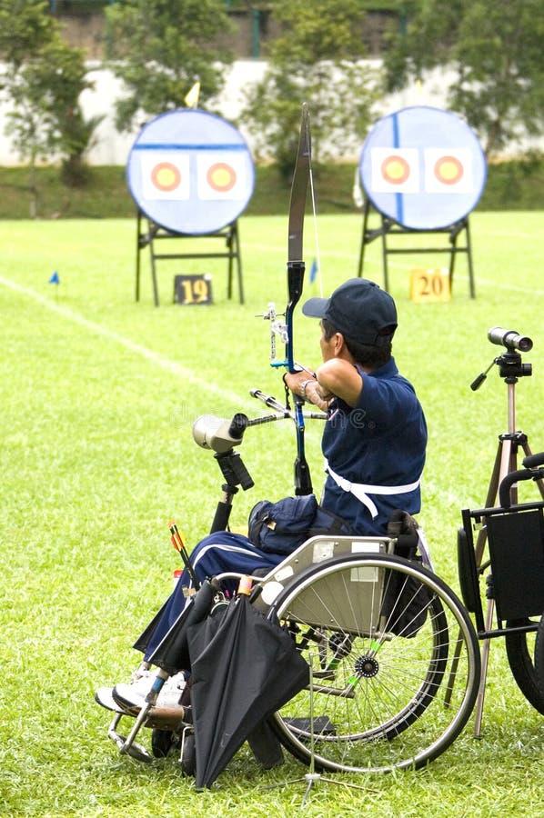 Tiro ao arco da cadeira de roda para pessoas incapacitadas foto de stock