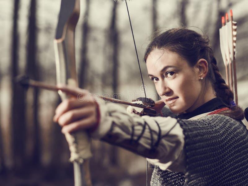 Tiro ao arco medieval, tiro da mulher foto de stock