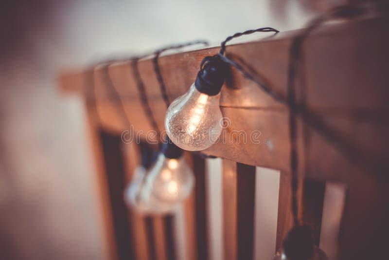 Tiro ascendente cercano de bombillas encendidas con los alambres negros que cuelgan en una superficie vertical de madera fotos de archivo libres de regalías