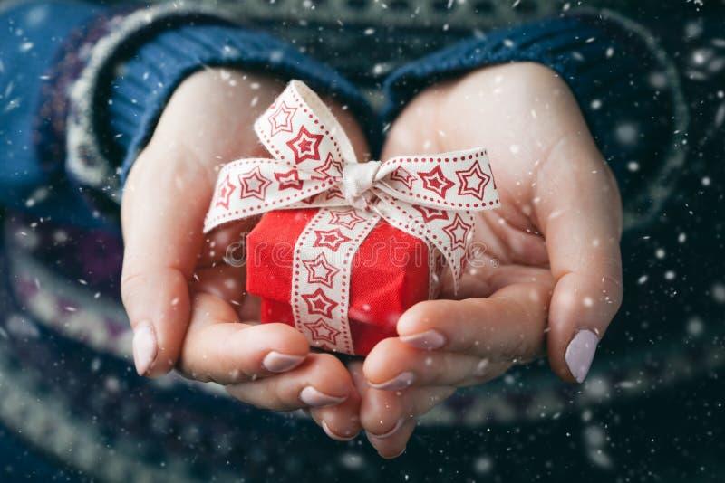 Tiro ascendente cercano de las manos femeninas que sostienen un pequeño regalo foto de archivo libre de regalías
