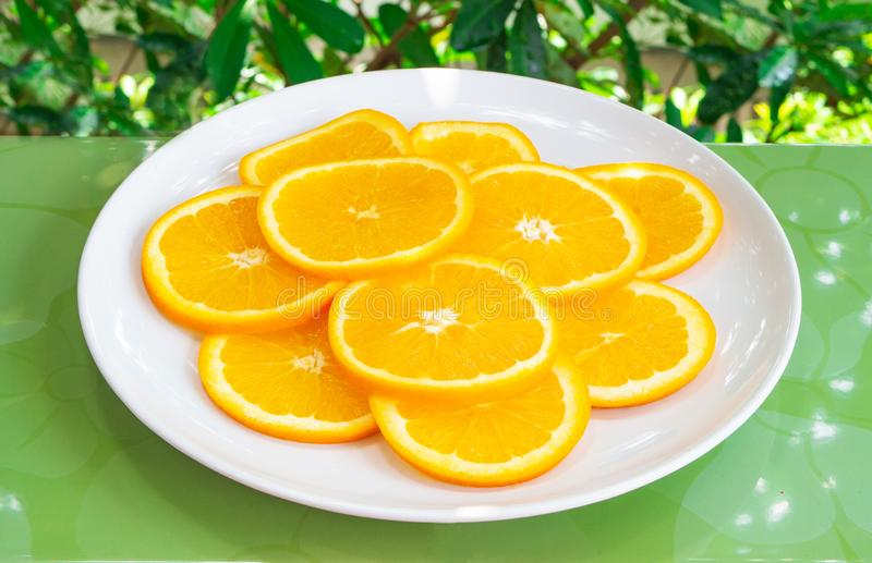 Tiro ascendente cercano de rebanadas anaranjadas en la placa blanca Consumici?n sana y vegetariana imagen de archivo libre de regalías