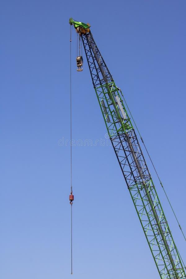 Tiro ascendente cercano del brazo verde de la grúa Cielo azul Gancho y carrete foto de archivo