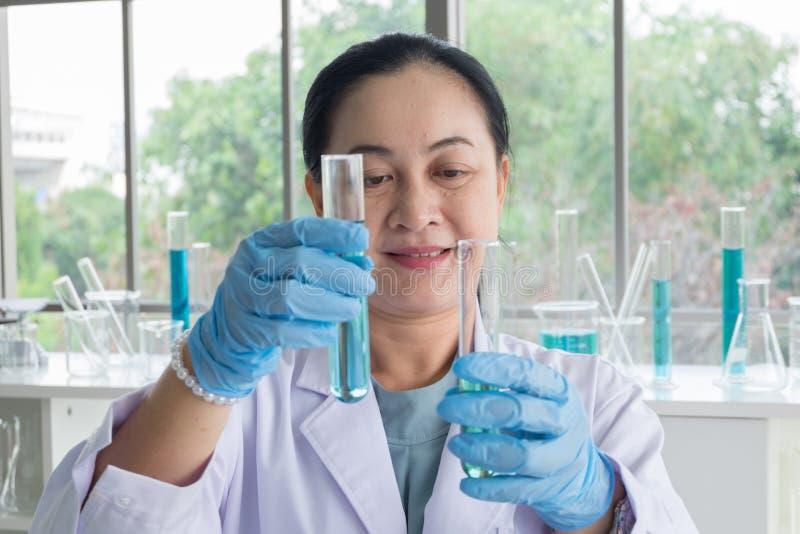 Tiro ascendente próximo, cientistas asiáticos da mulher da Idade Média tubo de ensaio perito que faz a pesquisa imagens de stock royalty free