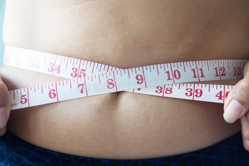 Tiro ascendente próximo da cintura de medição da mulher, conceito de dieta fotos de stock