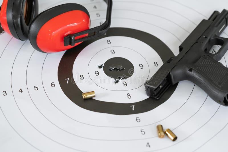 Tiro ascendente próximo de um alvo e de um bullseye de tiro com buracos de bala com a arma da pistola automática e a bala do cart fotos de stock royalty free