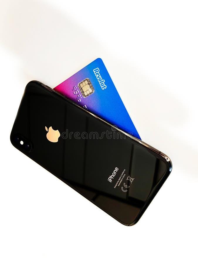 Tiro ascendente próximo do cartão do iPhone XS de Apple e de crédito de Revolut fotografia de stock