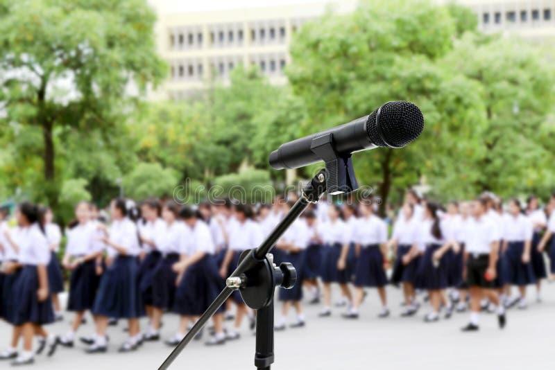 Tiro ascendente próximo do microfone na High School dos estudantes Blurred que anda para o fundo fotos de stock royalty free