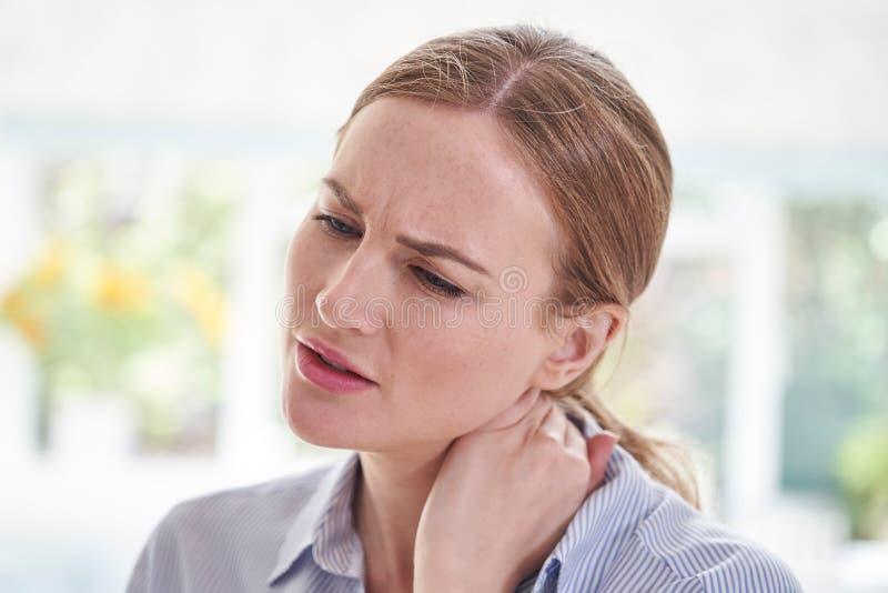 Tiro ascendente próximo do sofrimento da jovem mulher com dor do pescoço fotos de stock