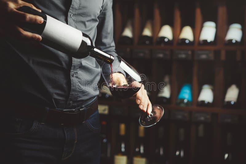 Tiro ascendente próximo do vinho tinto de derramamento do sommelier da garrafa no vidro no fundo subterrâneo da adega foto de stock