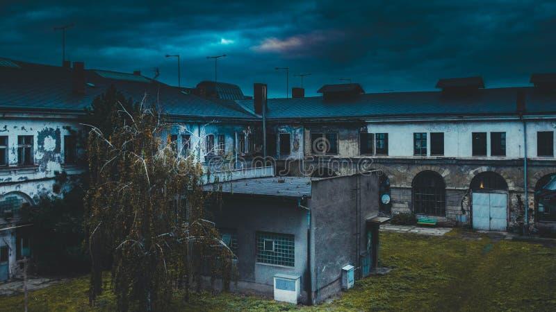 Tiro azul marino del patio trasero de un edificio viejo en la noche con el cielo nublado con trueno foto de archivo libre de regalías