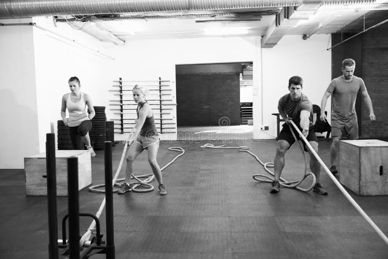 Tiro blanco y negro de la gente en el entrenamiento del circuito del gimnasio fotografía de archivo