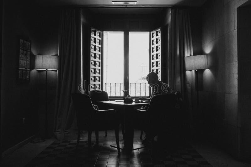 Tiro blanco y negro de la silueta de una sentada masculina en una silla alrededor de la tabla cerca de una ventana abierta imagenes de archivo