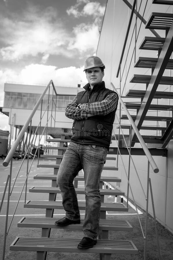 Tiro blanco y negro del arquitecto de sexo masculino joven que se coloca en stairca fotografía de archivo libre de regalías