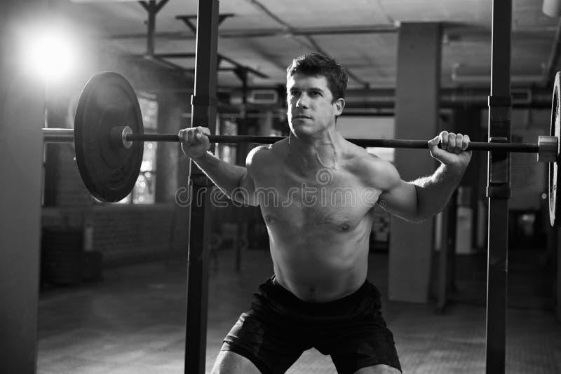 Tiro blanco y negro del hombre en pesos de elevación del gimnasio fotos de archivo libres de regalías